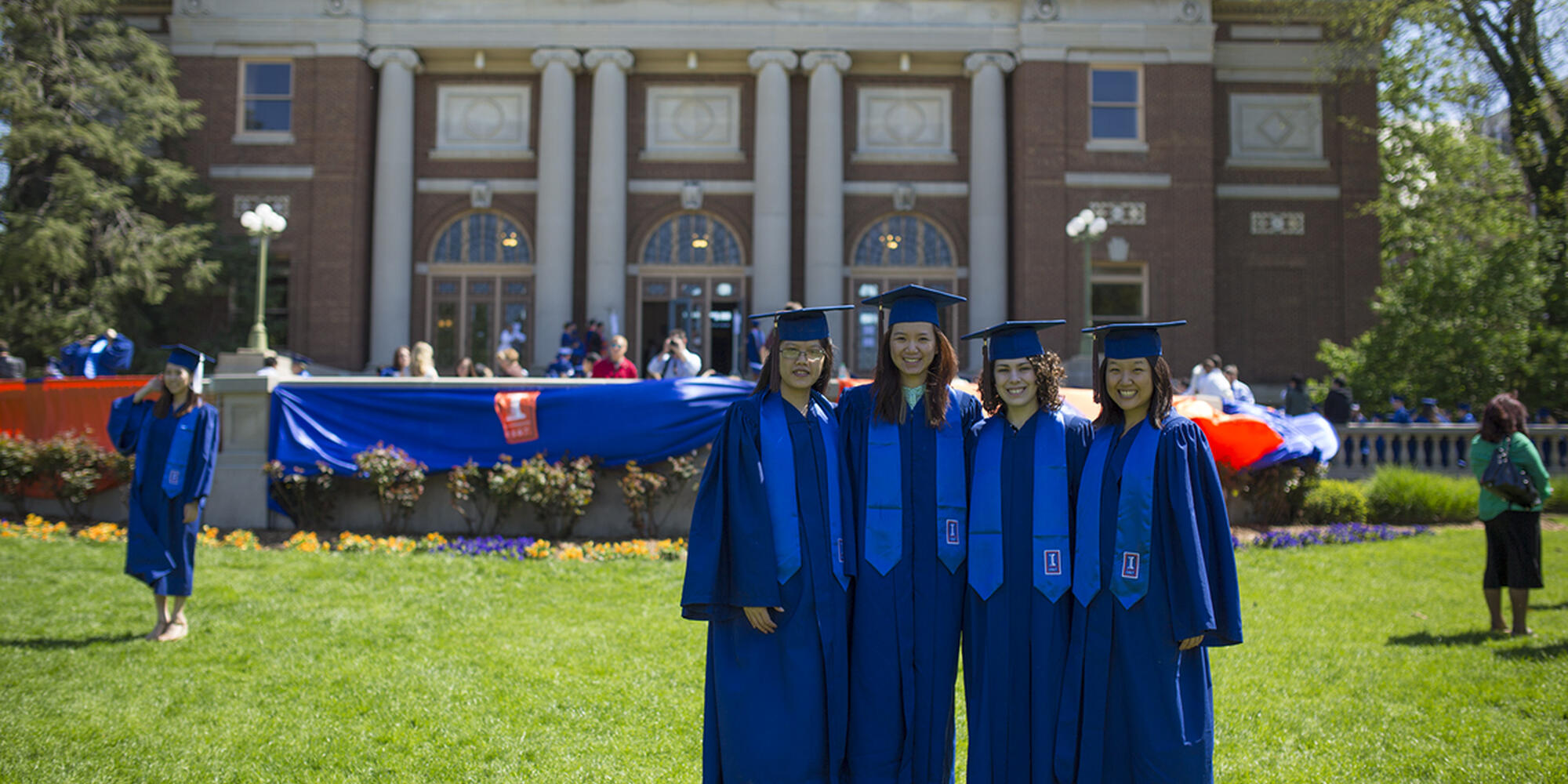 group of students in graduation gowns in front of Follinger Auditorium